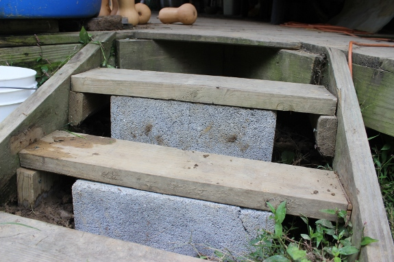 Using a cinder block to shore up porch steps.